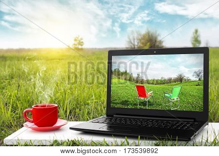 Laptop and cup of hot coffee on the background picturesque nature, outdoor office. Travel concept. Business ideas. The rest of nature. Beautiful landscape. Choice of travel.