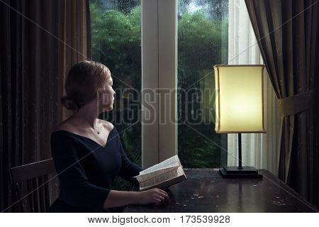 portrait of young woman with book sitting by the window