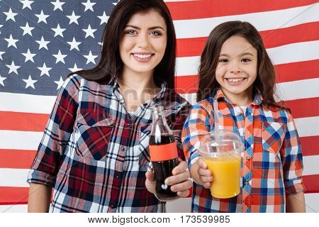 Enjoying tasty beverages . Happy young optimistic sisters celebrating American national holiday while standing against American flag and holding bottles with beverages