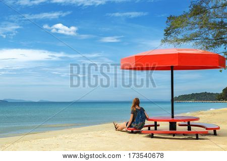 Young woman is resting under a beach umbrella and is looking at the sea, Sihanoukville, Cambodia