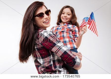 Sharing our joy with you. Young smiling delighted mother holding her daughter and celebrating American national holiday while standing against white background and expressing positivity