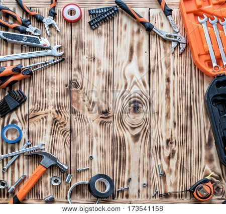 A set of working tools on a wooden background.