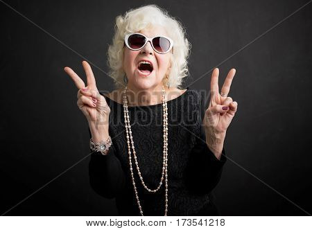 Cool grandmother showing peace sign with both hands