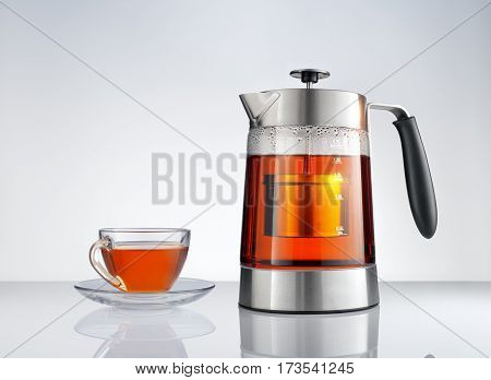 close up view of nice tea kettle and tea cup on grey back