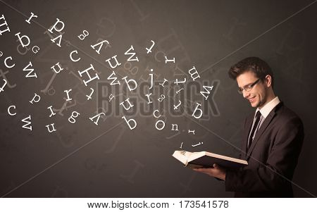 Casual young man holding book with white alphabet flying out of it