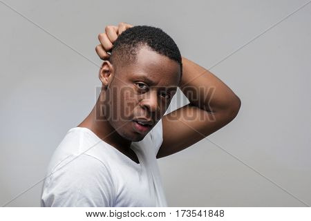 Thoughtful young african american man. Solving problems, worrying, anxiety. Portrait on grey background with free space for text.