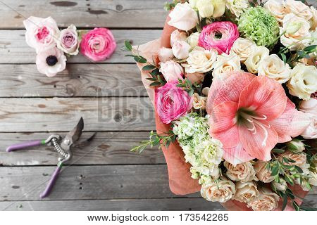mix flowers bouquet on wooden background. old rustic table, a coil of twine and garden secateurs. top view.