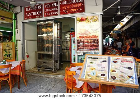 HERAKLION, CRETE - SEPTEMBER 19, 2016 - Spit roasted chickens at Grill House restaurant with a menu in the foreground along Odos 1821 Heraklion Crete Greece Europe, September 19, 2016.