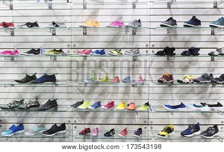 lots of sports sneaker shoes on sale, displayed.