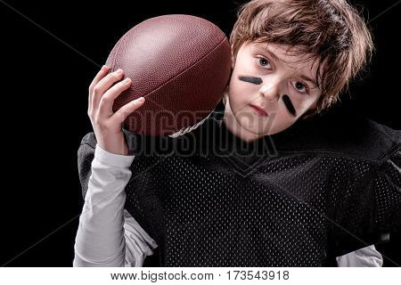 Upset boy american football player holding rugby ball and looking at camera