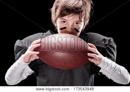 Serious boy american football player in protective sportswear holding rugby ball