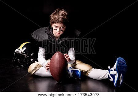 Serious little boy american football player sitting with ball and looking at camera