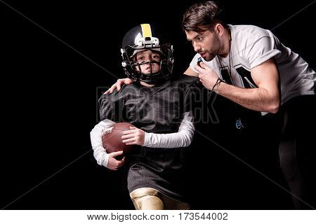 Coach looking at boy american football player running with ball