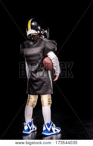 Back view of little boy american football player in uniform holding ball