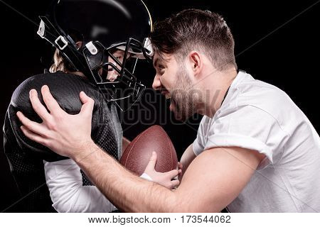 Side view of trainer screaming at boy american football player on black