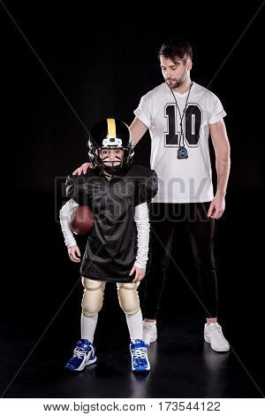 Full length view of boy american football player standing with ball near coach
