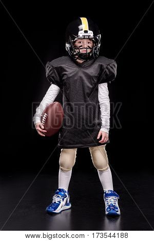 Full length view of little boy american football player in uniform holding ball