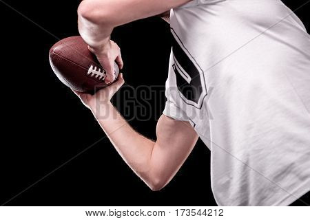 Low angle partial view of man in white t-shirt holding rugby ball on black
