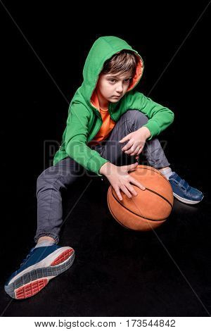pensive boy sitting on floor with basketball ball and looking away on black