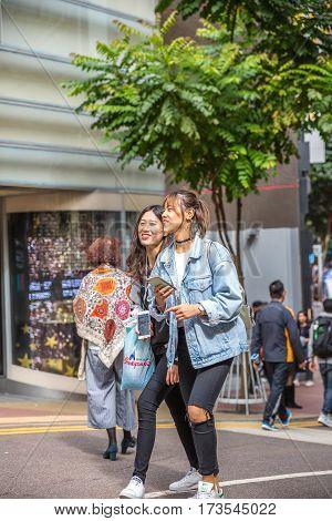 Hong Kong, China - December 6, 2016: couple of modern young girls talking friendly in Causeway Bay, Jardine's Crescent street market.