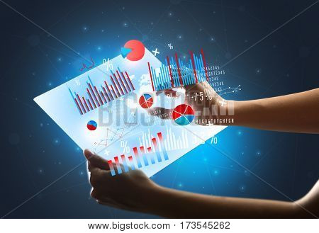 Young female hand holding a tablet with red and blue charts