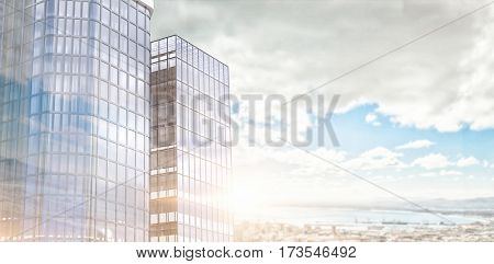 Low angle view of glass building against landscape of city and cloudy sky