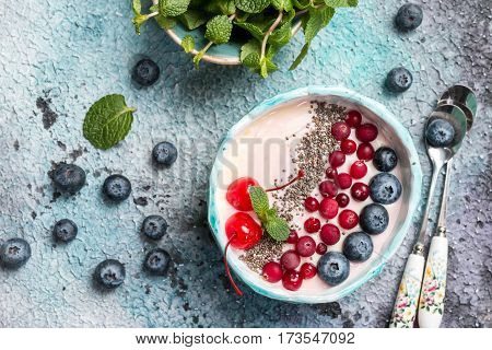 Light greek yogurt or cream dessert with chia seeds, goji and fresh berry served in blue bowl, top view