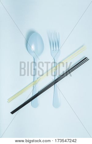 Raw spaghetti on blue spoon and fork and blue background