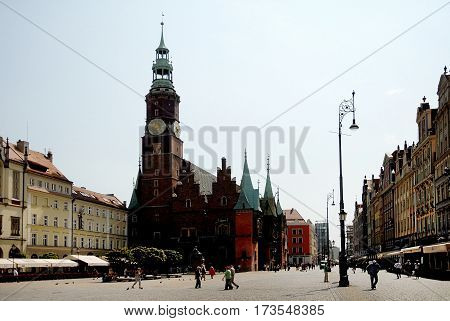 Wroclaw Poland - July 17 2014: Market Square and Wroclaw Town Hall built in Gothic style of architecture are one of the main landmarks and tourist attractions in the city.