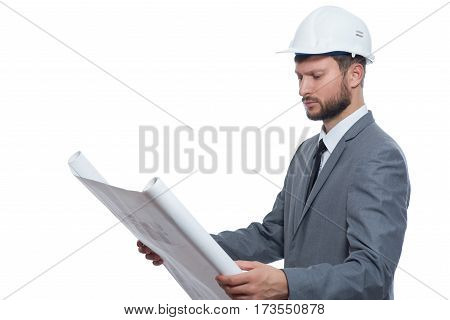 Experienced engineer. Serious young male businessman engineer wearing protective hardhat looking at blueprints isolated on white copyspace business industry engineering architecture designer concept