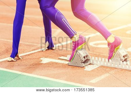 Sportswoman at the starting blocks before sprint running event