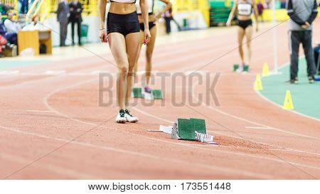 Sportswoman standing near starting blocks before sprint running event