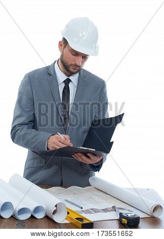 Making notes. Vertical portrait of a professional male architect in a protective hardhat making notes on his clipboard isolated profession writing information specialist experienced businessperson