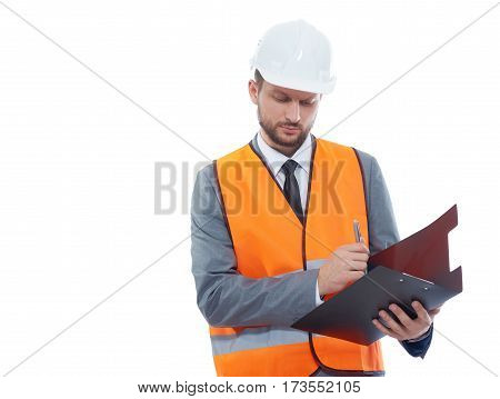 Building industry worker. Studio shot of a male constructionist wearing fluorescent safety vest and a hardhat making notes on his clipboard isolated on white copyspace profession builder concept