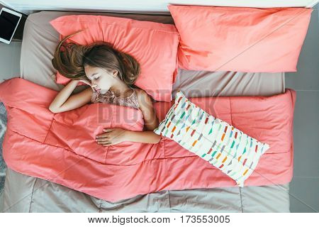10 years old pre teen kid girl sleeping in the bed with pink bedding, top view