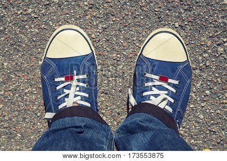 denim sneakers on his feet shod top view