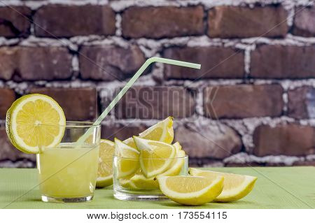 Lemon juice with glass and straw and freshly cut lemons
