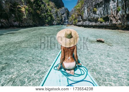 Back view of the young woman in straw hat relaxing on the boat and looking forward into lagoon. Travelling tour in Asia: El Nido, Palawan, Philippines.
