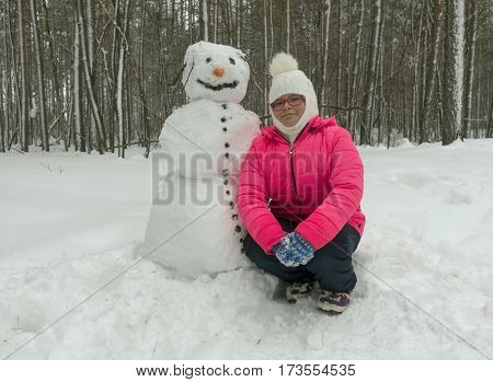 Little girl with a snowman in the winter forest