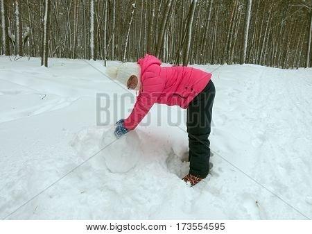 Little girl makes a snowman in the winter forest