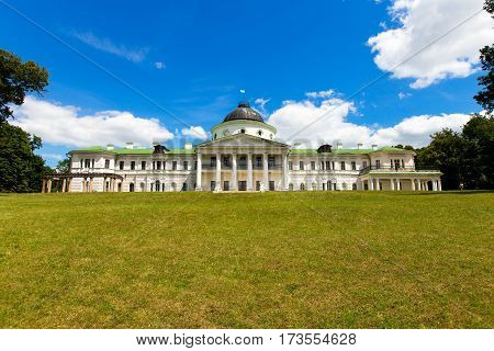 old white mansion with a tower. in the foreground is a meadow. summer day blue sky with clouds