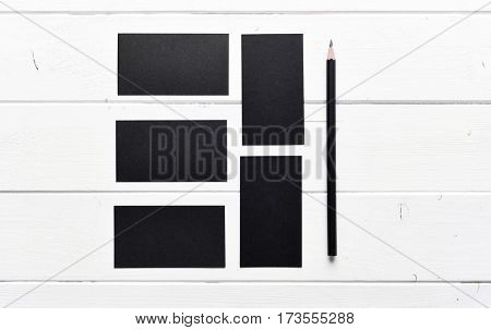 set of black business cards with pencil on a white wooden table
