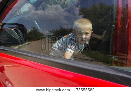 closed a boy in a red car and trying to get through the doors Car