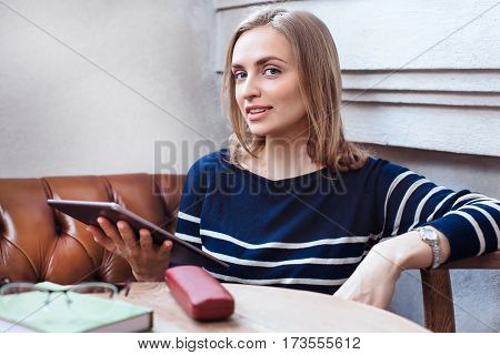 Beautiful young woman sitting in cafe and use tablet. Smiling and looking at camera. Consept of studing and working online. Beautiful woman with digital tablet, while relaxing after work