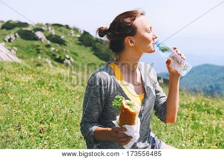 Beautiful young woman drinking still water and eating vegetarian sandwich on the nature background in the mountains. Velika Planina or Big Pasture Plateau in the Kamnik Alps Slovenia.