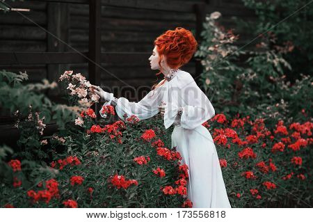 Redhead woman. Beautiful red-haired woman with a high hair in an old white dress in the park. Woman in park. The Victorian era woman. Historic costume. Woman in garden. White Queen. Princess castle. Stylish woman