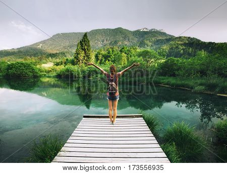 Young Woman With Raised Arms Up On The Nature Background.