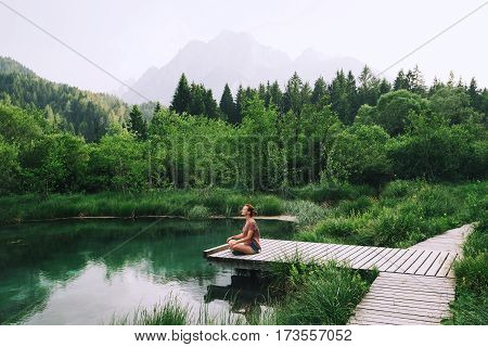 Woman Doing Yoga And Meditating In Lotus Position On The Nature.