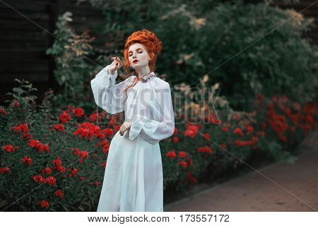 Beautiful red-haired girl with a high hair in an old white dress in the park. The Victorian era beauty style. Historic costume. White Queen. Princess castle. Historic beauty style. Photography in beauty style. Beauty concept. Princess fashion dress.