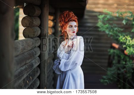 Beautiful elegant red-haired girl with a high hair in an old white dress in the park. The Victorian era. Historic elegant costume. White Queen in elegant dress. Princess castle